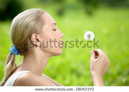 The blonde sits in park on a grass with a dandelion in hands - stock photo