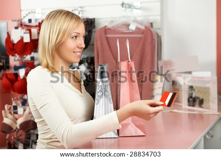 The blonde with packages in an underwear boutique holds a credit card in a hand - stock photo