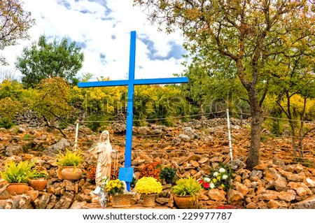 The Blue Cross and Statue of Blessed Virgin Mary at Apparition Mountain in Medjugorje among grey rocks and green trees and weeds - stock photo