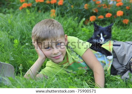 The blue-eyed boy on a grass - stock photo