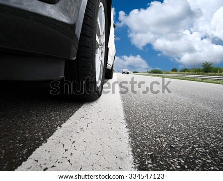 The blurred car and blue sky with clouds - stock photo