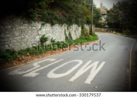 The blurry focus of slow wording street sign represent the road traffic sign concept related idea. - stock photo