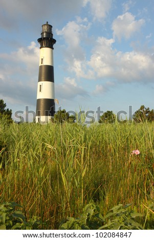 The Bodie Island lighthouse over marshes of the Cape Hatteras National Seashore on the Outer Banks of North Carolina against white clouds and a blue morning sky vertical - stock photo