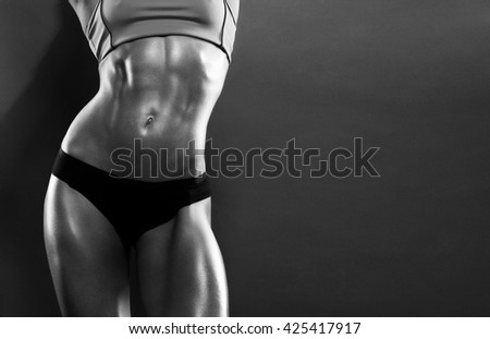 The body of a young athletic girl on dark background - stock photo