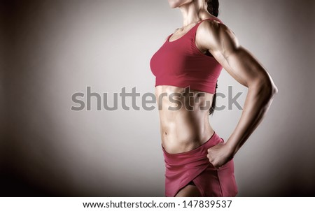 The body of a young athletic girl on gray background - stock photo