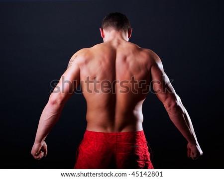 The bodybuilder back isolated on black background - stock photo