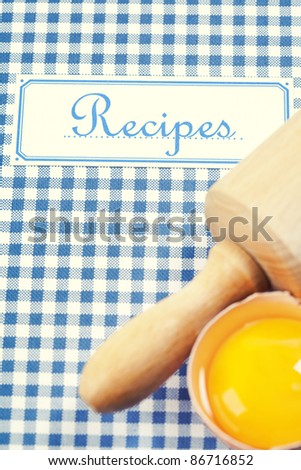 The book of recipes with egg and rolling pin - stock photo