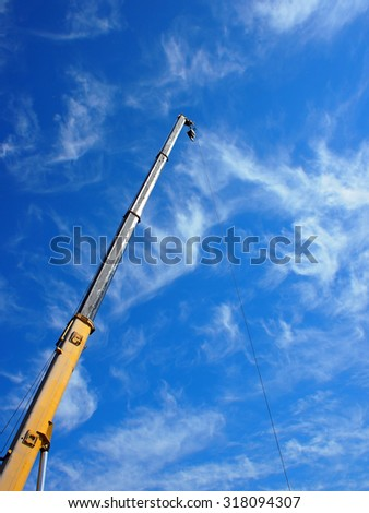The boom of the crane on a diagonal against a blue sky with white cirrus clouds - stock photo