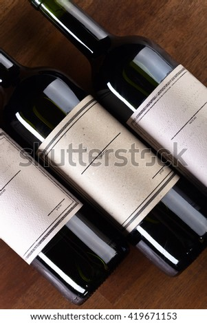 The bottles of red wine on old wooden table - stock photo