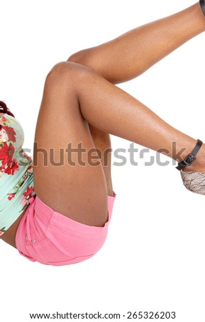 The bottom and legs of a young slim African American woman sitting on the floor in pink shorts, isolated for white background.  - stock photo