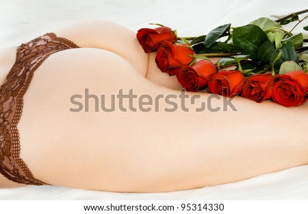 The bouquet of red and white roses lays between beautiful, young, harmonous female legs - stock photo
