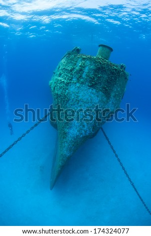 The bow of a massive shipwreck, the Kittewake, is anchored to a sandy seafloor in Grand Cayman. This ship was sunk intentionally to act as an artificial reef and as an attraction for scuba divers. - stock photo