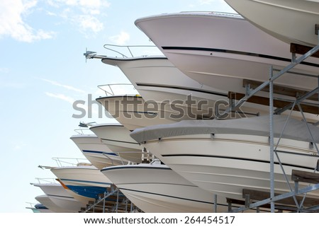 The bows of boats sticking out of a boat storage rack in a marina. - stock photo