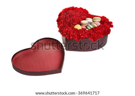 The box in the form of heart, is filled by flowers and cookies. Red carnations, white background. - stock photo