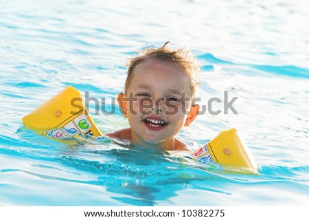The boy bathes in pool,  hot summer day - stock photo