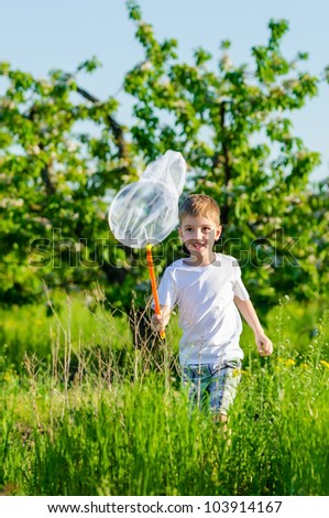 The boy catching a net of butterflies in a blossoming garden - stock photo