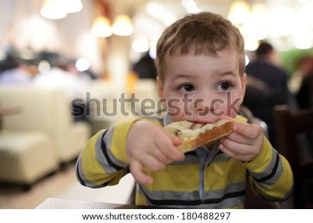 The boy eats bruschetta at a restaurant - stock photo
