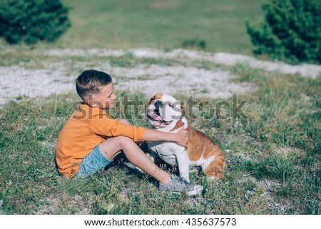 The Boy hugging his dog. A boy with an english bulldog on a field. - stock photo
