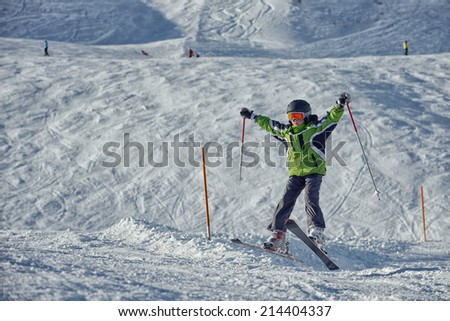The boy in a green jacket on skis in mountains - stock photo