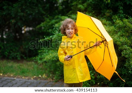 The boy in a raincoat with an umbrella in hands. The cute little fellow dressed in a yellow raincoat holds a yellow umbrella. He looks in the camera. Behind his back magnificent green vegetation. - stock photo