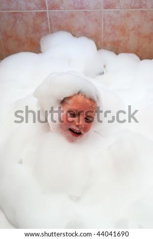 The boy in bath the filled foam - stock photo