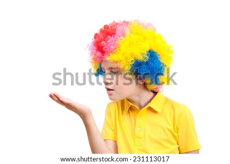 The boy in clown wig blowing on the palm - stock photo
