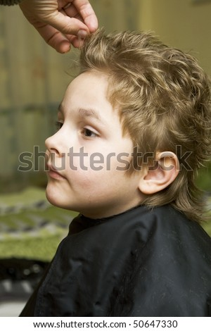 The boy in the barber shop, he gets the hair - stock photo