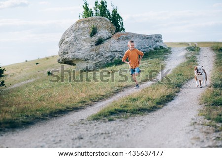 The boy in the orange jacket with a bulldog running along the field - stock photo
