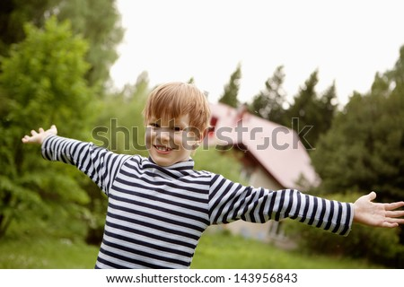 The boy in the striped sweater/ Eight years old boy spread his hands and smiling happily - stock photo