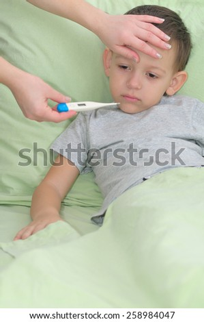 The boy is sick. Mom measures temperature using a thermometer - stock photo