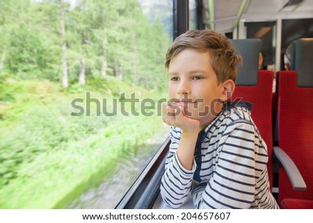 the boy is traveling in a train - stock photo