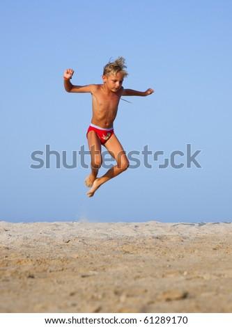The boy jumps up on the sandy beach near the sea - stock photo