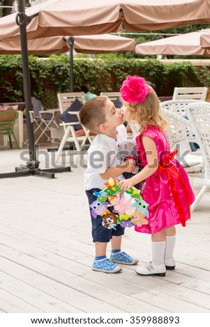 The boy kid gives flowers and kissing girl child on birthday. Little adorable girl celebrating 3 years birthday. Childhood. - stock photo