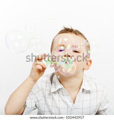 The boy lets go soap bubbles. The little boy and soap bubbles. Carefree. - stock photo