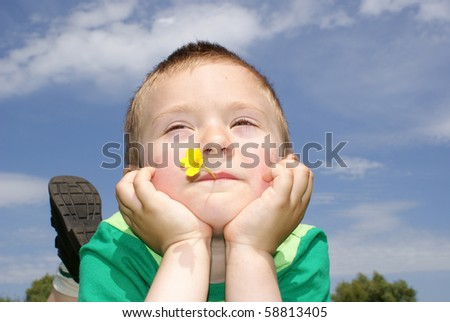 The boy lies in a meadow with flowers in the mouth - stock photo