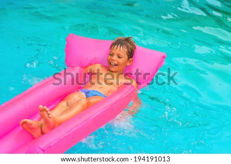 The boy lies on a mattress in the pool - stock photo