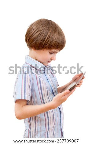 the boy looks at the screen of a tablet PC - stock photo