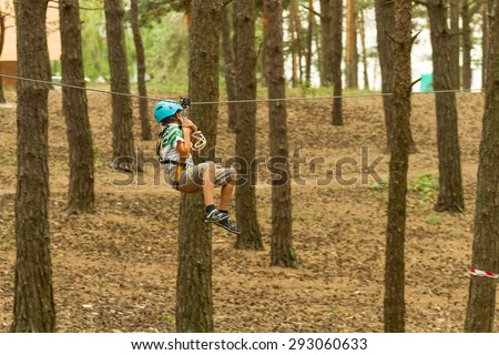 The boy moves down a steel rope at a training session tourism. motion blur - stock photo