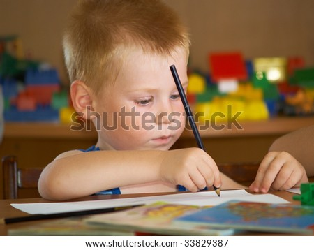 The boy of 2 years is engaged in a children's room - stock photo
