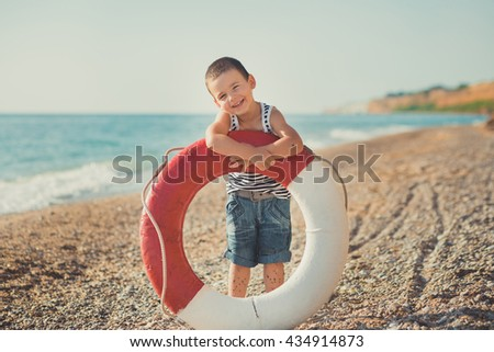 The boy on the beach with a lifebuoy.   A smiling boy on a beautiful beach. - stock photo