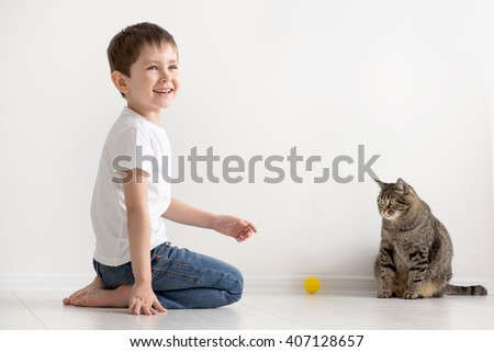 the boy plays on a floor with a cat with a yellow ball - stock photo