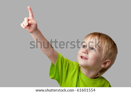 The boy points his finger upward. Half-length portrait, arms down. Gray  background - stock photo