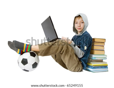 The boy sits with the laptop, a ball, books - stock photo