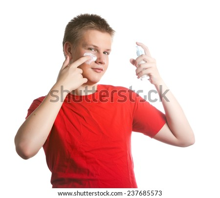 The boy, the teenager with a cream for a problem youthful skin, against spots - stock photo