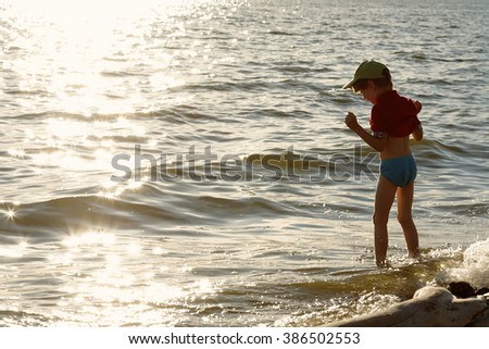 The boy timidly enters the sea and laughing. Summer evening. - stock photo
