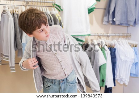 The boy tries on clothes in the childrens clothing store - stock photo