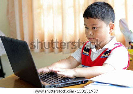 The boy was playing with my notebook. - stock photo