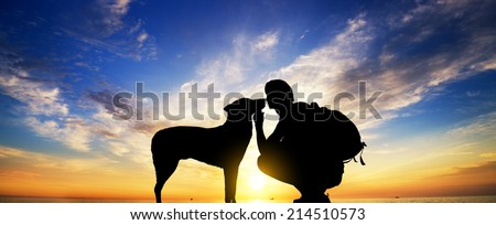 The boy with a dog against to sunset. - stock photo
