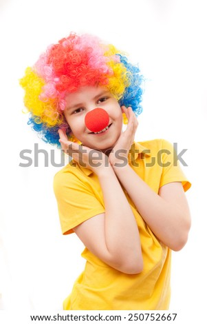 the boy with a red clown nose and bright wig - stock photo
