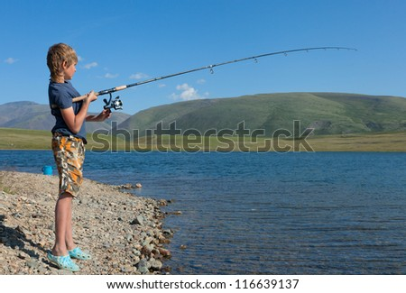 The boy with a spinning catch grayling. Beautiful fish in mountain lakes and rivers - stock photo
